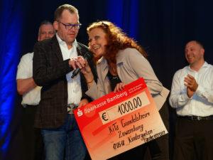 Zu Beginn des Abends überreichte Organisator Stephen Goldfarb einen Scheck über 1.000 Euro, den Erlös der letzten A Cappella Nacht, an eine Erzieherin des Gundelheimer Kindergartens.