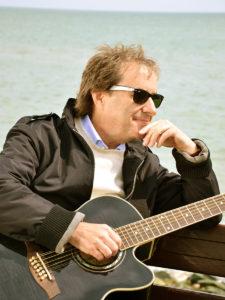 Chris de-Burgh mit Gitarre am Strand