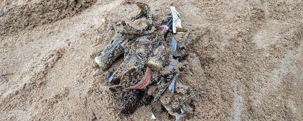Sofortige Reinigung nach Hinweis auf zerbrochene Flaschen im Sand