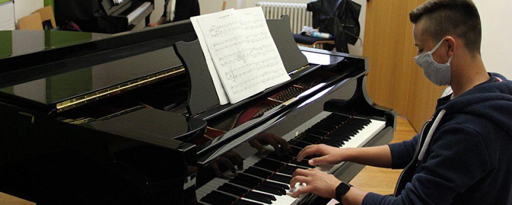 Mit Mundschutz am Klavier…